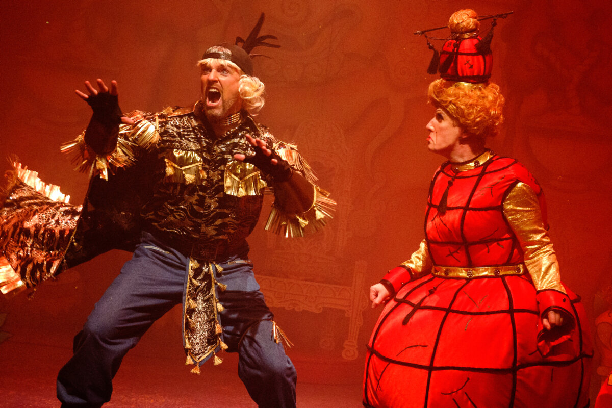 Production shot of Ben Harlow as Abanazar in an action pose with his hands like cat claws and Philip Elvy as Widow Twankey in a lantern dress scowling at Abanazar.
