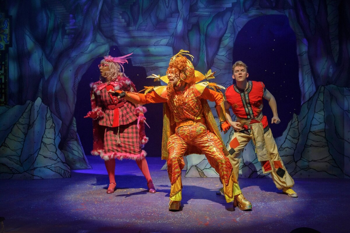 Production shot of Emily Mae as Celia Siri, Ben Barrow as the Genie and George Olney as Aladdin standing in a line, leaning to the left and looking into the distance.