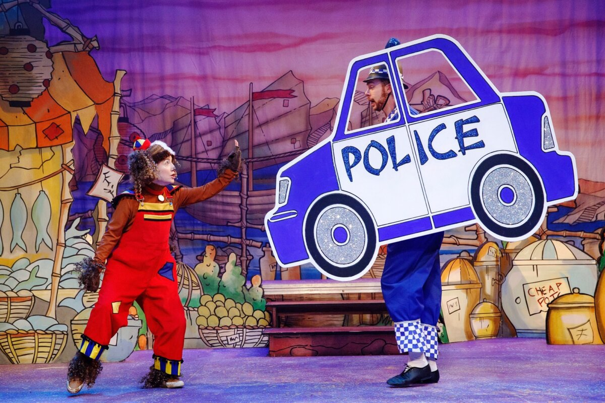 Production shot of Susan Harrison as Wishee Washee holding her hand up in a stop sign to Ben Barrow as PC Correct in a prop police car.