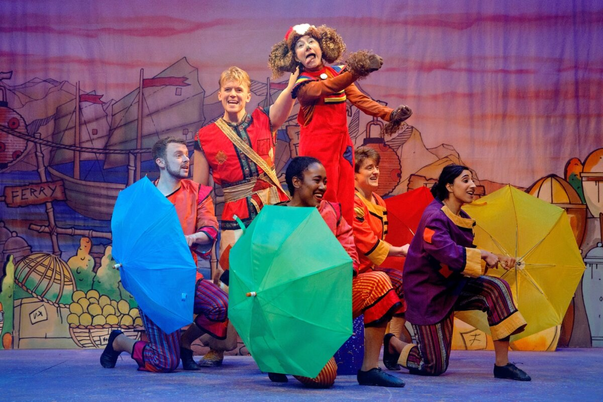 Production shot of four actors in villager costumes holding umbrellas to mimic wheels of a car, with Susan Harrison as Wishee Washee miming driving the car and George Olney as Aladdin behind.