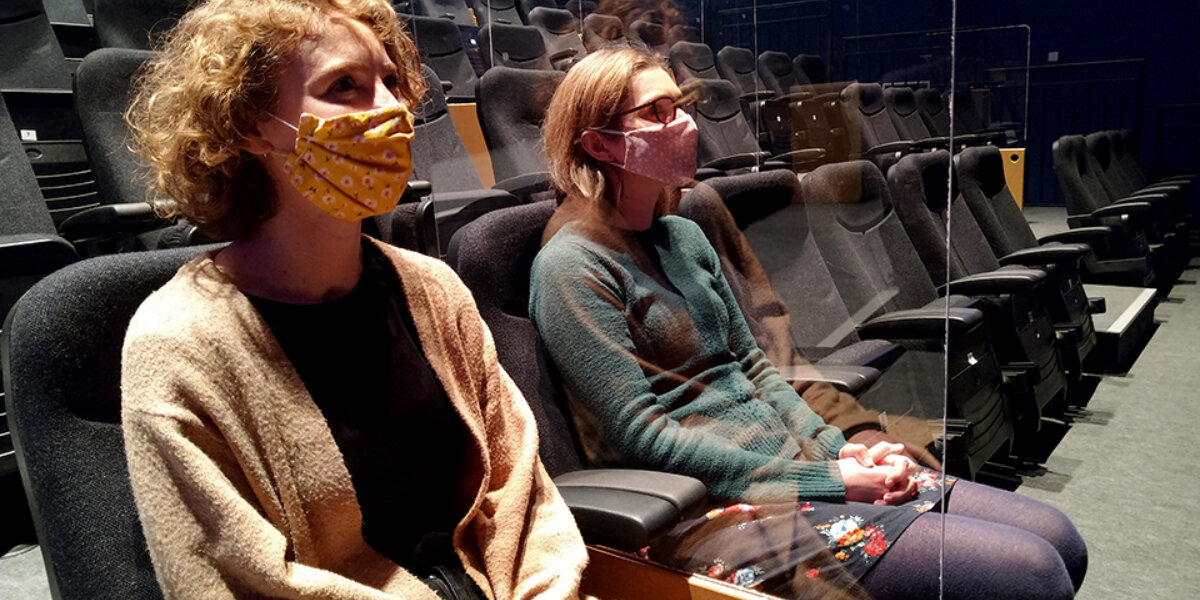 Two females seated with masks on with a clear perspex divider between them.
