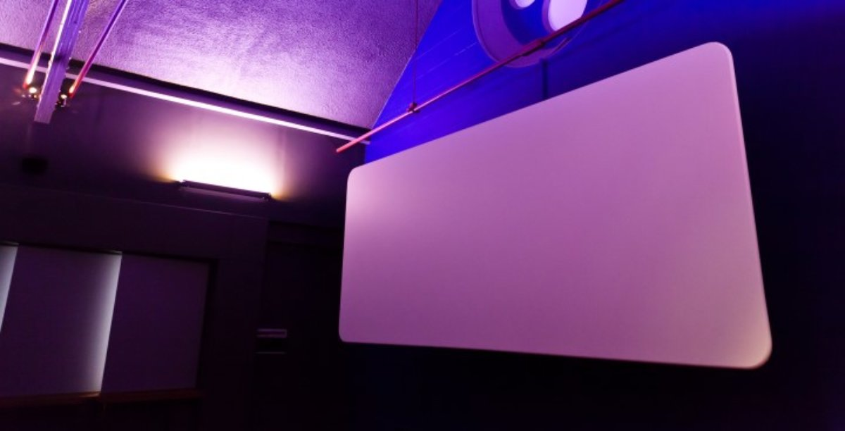 A 40 seat cinema with red carpet and navy dark seats, pointing towards a cinema screen.
