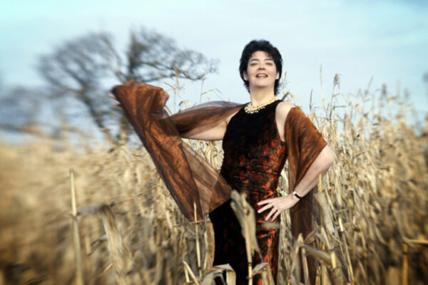 Hilary dressed in a brown evening dress with a shawl standing in a  field of straw.