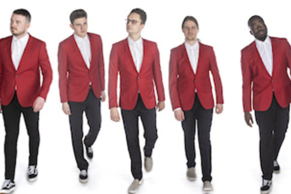 5 male singers are standing in a line, dressed with a red jackets, black trousers and trainers. The background is white.