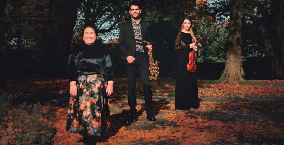 A woodland background with three musicians standing in a row. The middle musician is holding a saxophone, the musician on the right is holding a violin.