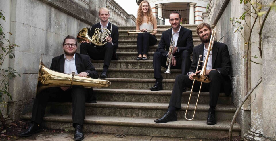 5 musicians holding brass instruments and in black and white attire are sat tiered on stone steps