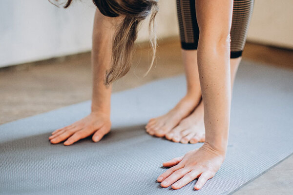 Woman standing and stretching to touch the yoga mat at her feet.
