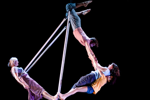Four performers balanced on a wire