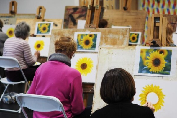 A diagonal row of participants with their backs to the camera, each sat in front of their easel painting sunflowers.