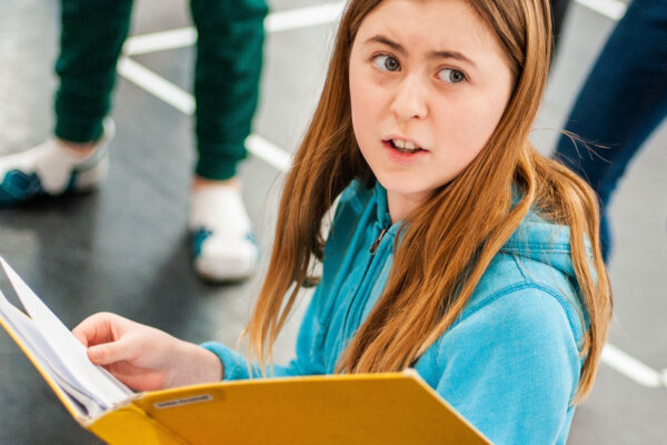 A girl in a blue jumper holds a yellow folder, as if she is reading a script.