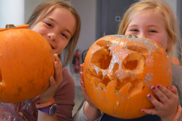Two young females are smiling and each holding a carved pumpkin.