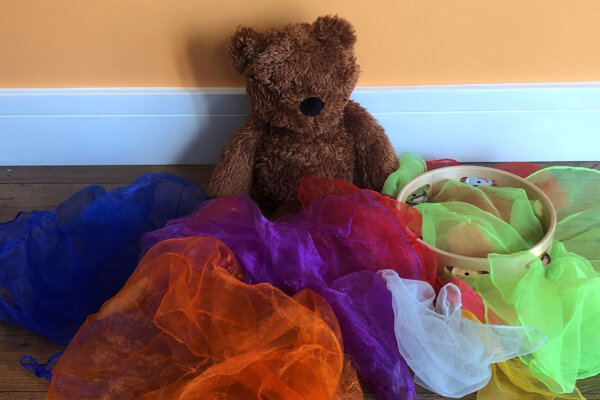 A small brown teddy bear sits propped up against a wall, surrounded by colourful scarfs.