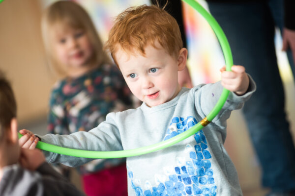 A photo a child holding a green hoop in the air.