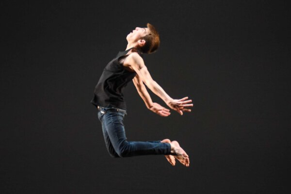 An action shot of a young male dancer leaping in the air with his back arched and his arms and legs pointing backwards.