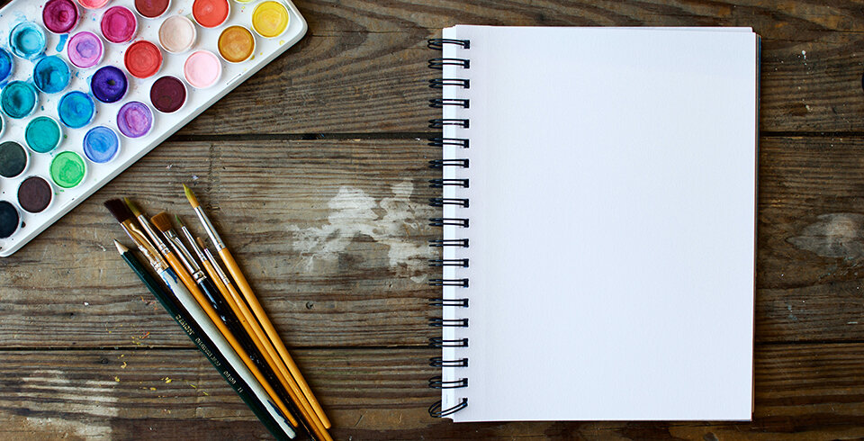 A notepad, paint brushes and paints.