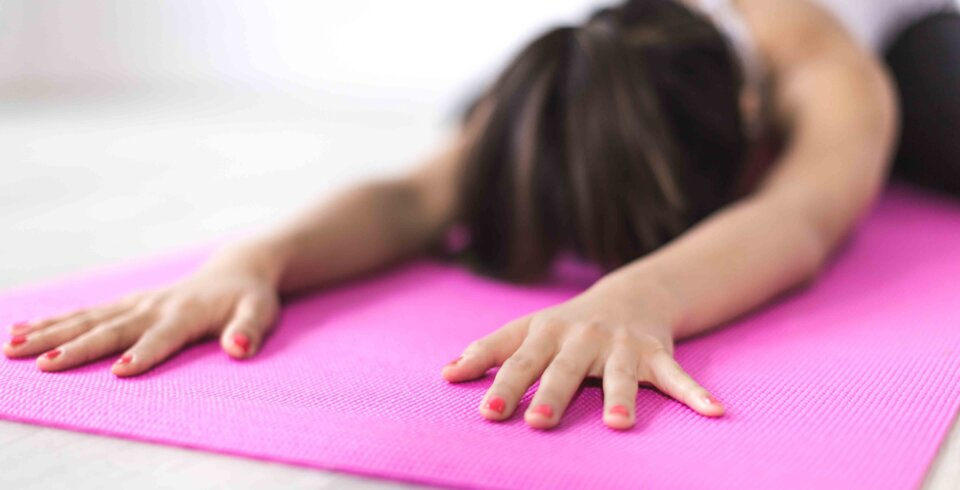 A pink Pilates mat and a female participant facing down towards the floor in a child's pose.