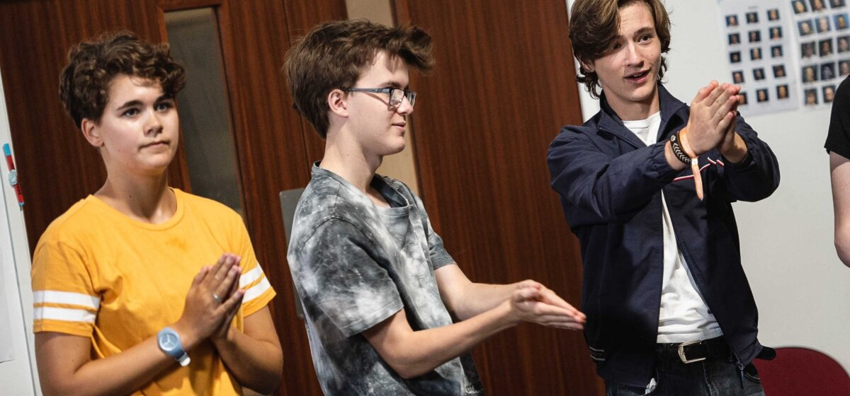 Three young performers with short brown hair take part in a warm up group activity during rehearsals.