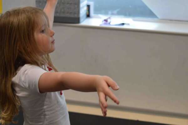 A young girl aged around 5 with blonde hair, poses with her arms outstretched.