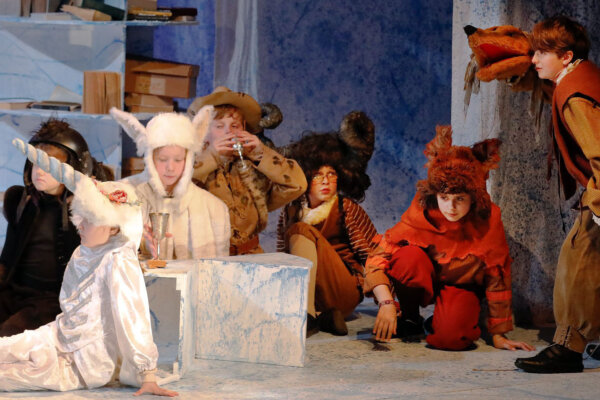 A group of boys and girls are in a variety of animal costumes on stage. Some are in white whilst others are in furry brown costumes. The background set is blue, with some books on a shelf.