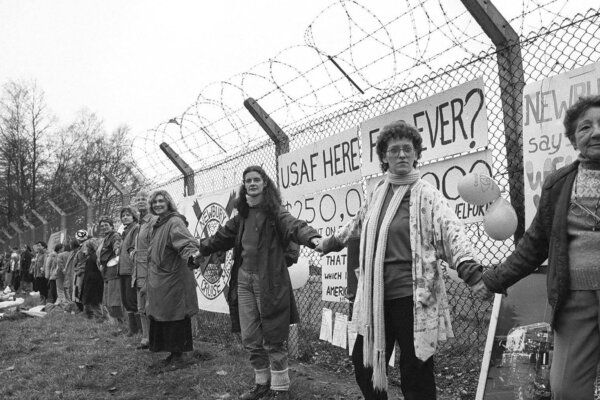 A line of women holding each other's hands in front of a wire fence.