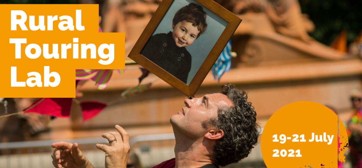 A photograph of a man balancing a framed photo of a young child on his nose. To the left of him says the words RURAL TOURING LAB in bold white font, behind an orange background. On the right of the image is a circle in the same orange colour. Over the top are the words 19 - 21 July 2021.