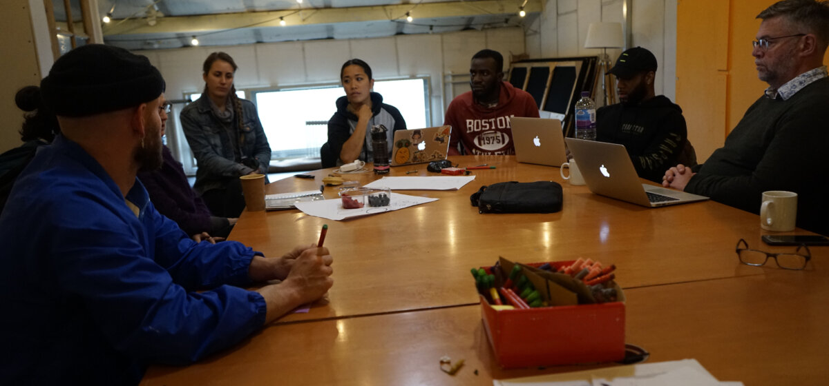 A group of seven men and women of different ages and races sit around a large wooden table. They are talking to each other and some of them have laptops on the table, whereas others have paper.